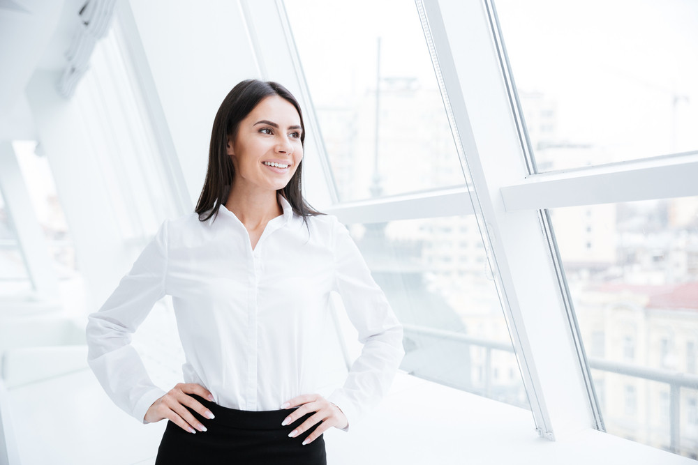 Business woman standing near the window in office with arms at hips and looking away