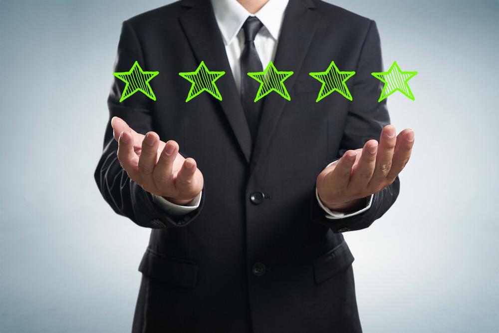 Businessman holding five star rating.