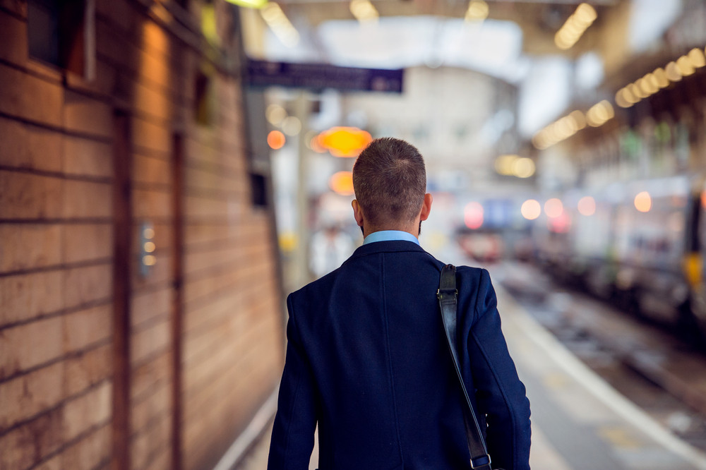 Businessman in suit walking at the train staition platform, back view, rear viewpoint