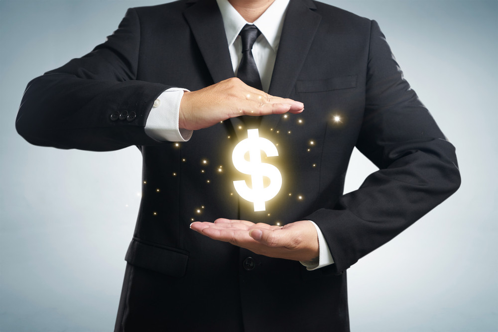 Businessman in suit with two hands in position to protect something (focus on hand, blur out the suit). It indicates many aspects such as car insurance coverage, support, assurance, reliability.