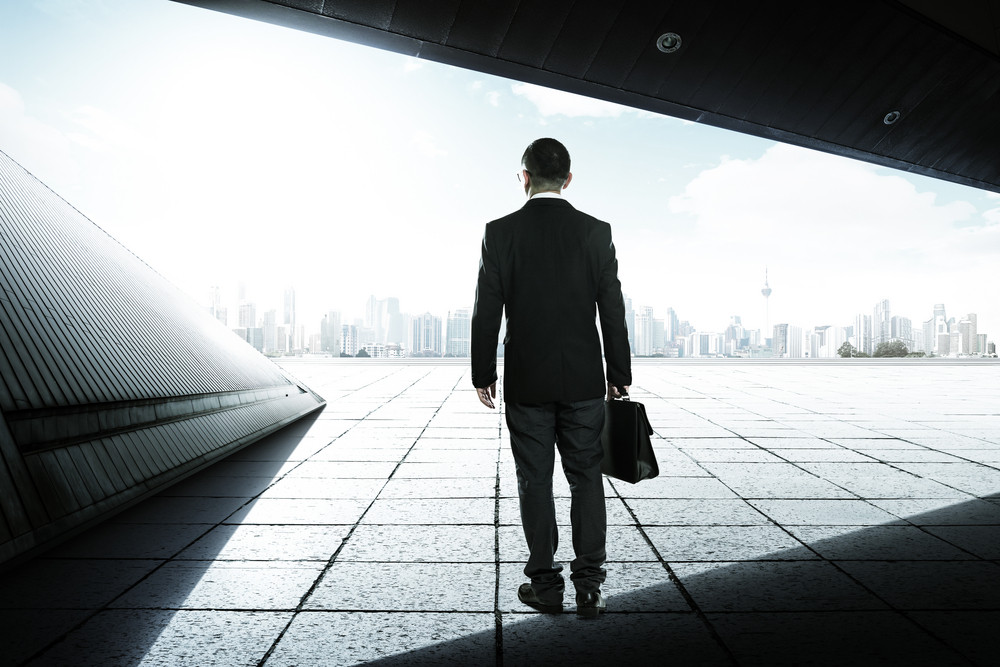 Businessman on the geometry design roof top balcony and looking at the city with skyscrapers