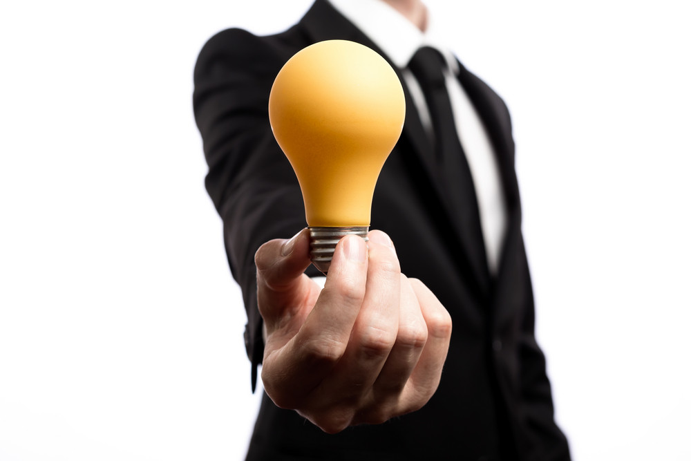 Businessman showing a lightbulb, inspiration concept, on a white backround