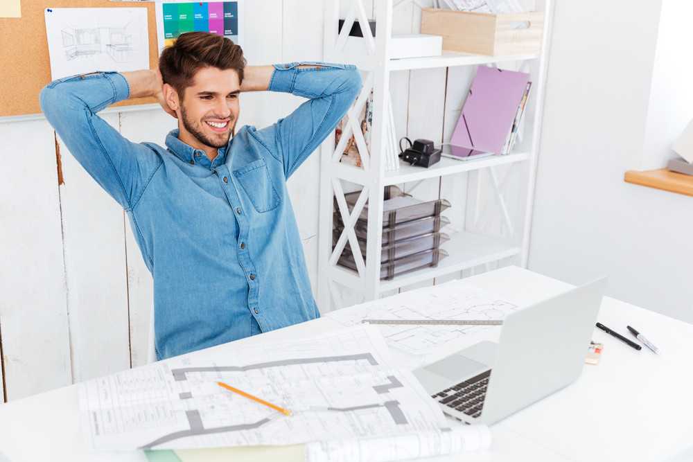 Businessman stretching hands at his workplace in office and looking at laptop