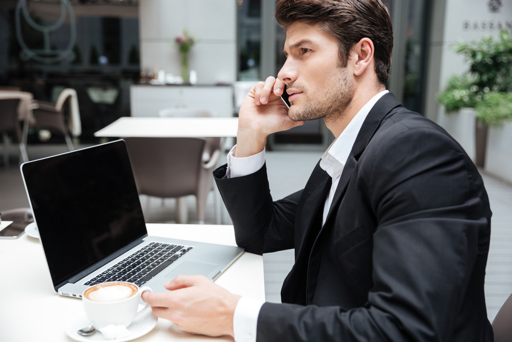 Businessman using blank screen laptop and talking on cell phone in outdoor cafe