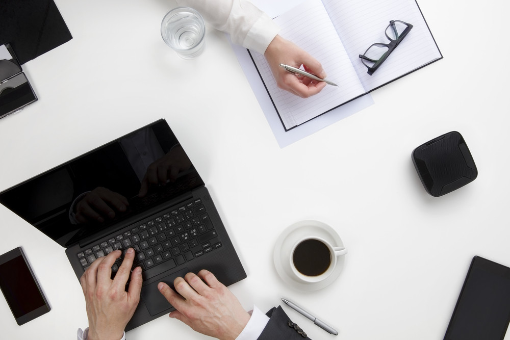 Businessman Using Laptop While Female Colleague Writing In Diary