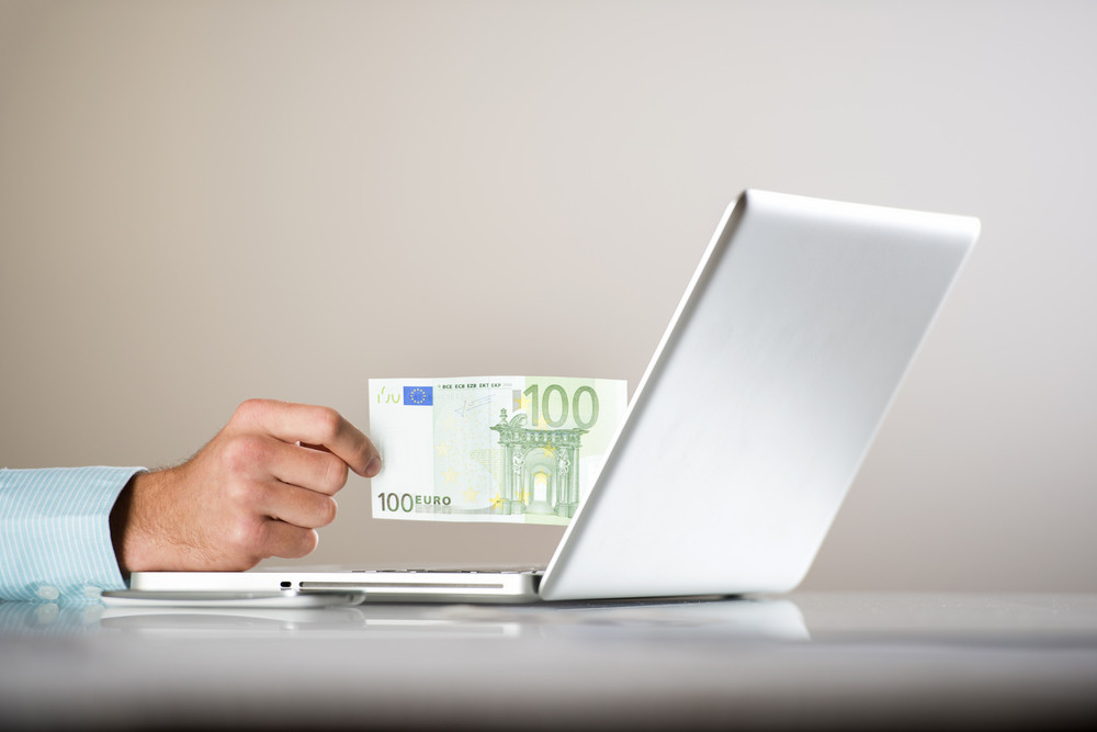 Businessman with laptop and money in his office