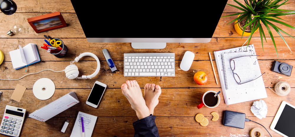 Businessman working in his office with feet on desk. Smart phone, tablet and various office supplies around the workplace. Flat lay.