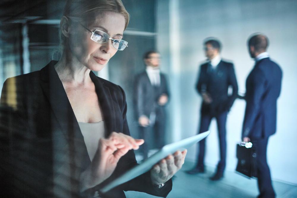 Businesswoman in eyeglasses using digital tablet in working environment