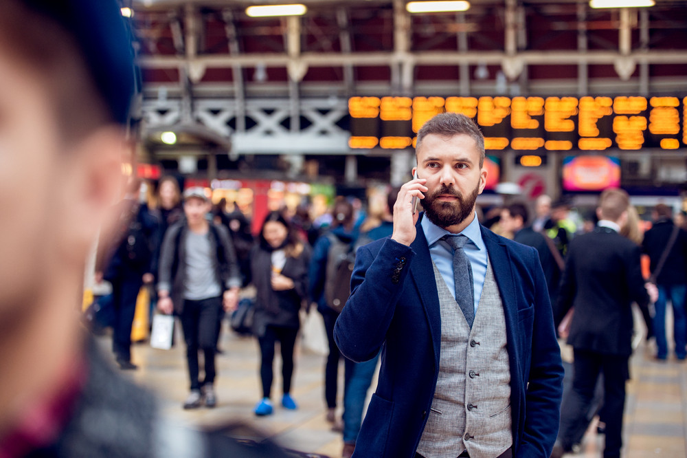 Busy hipster businessman holding a smartphone, making a phone call,  standing at the crowded station