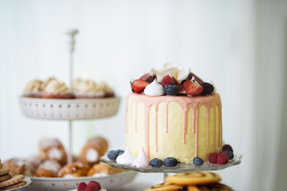 Cake with various berries and meringues on a stand. Cupcakes and tubes of pasty on other stand. Studio shot.