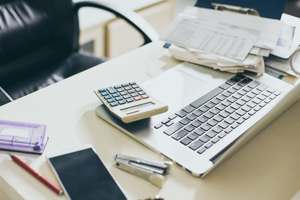 Calculator, documents and laptop on the table of business person