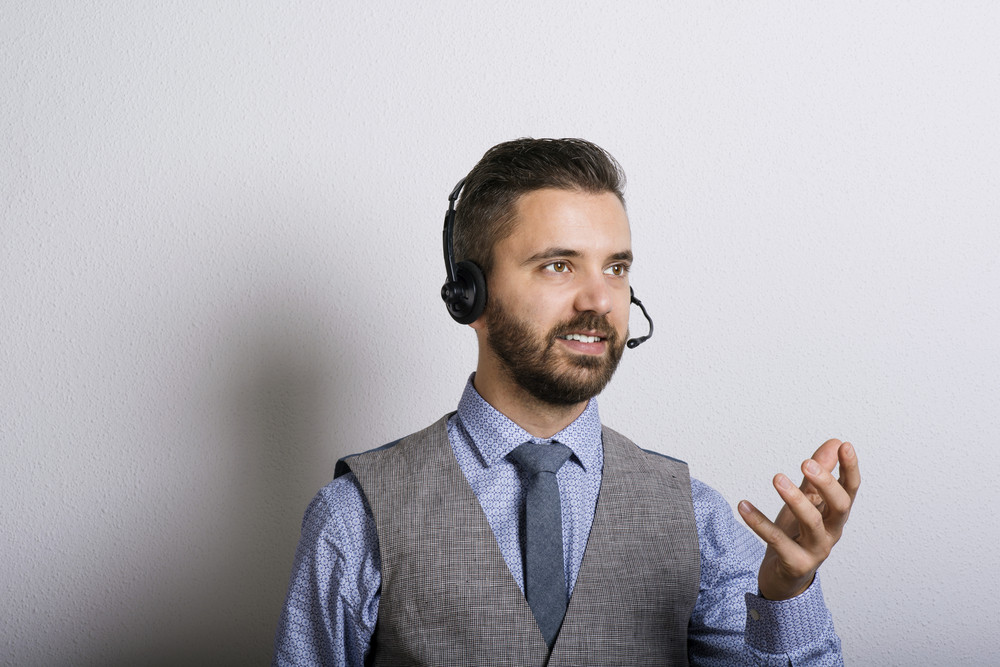 Call center operator isolated on white. Young handsome hipster man with headset.