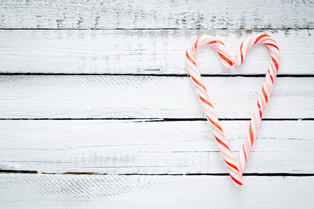 Candy cane heart on wooden background