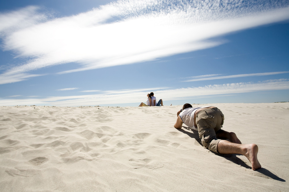 Careful photograpther taking shots of relaxing couple sitting back to back on sandy beach against blue sky