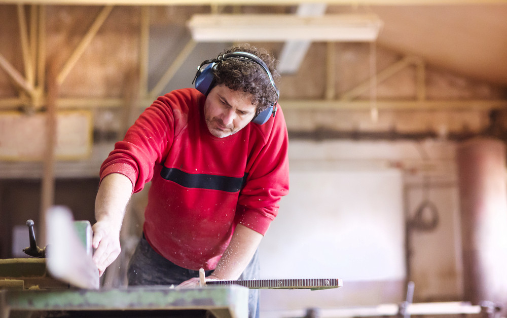 Carpenter working with electric wood planer in his workshop