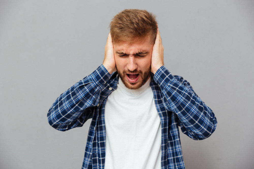 Casual bearded man covering his ears and shouting isolated on a gray background