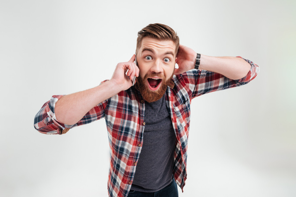 Casual surprised man in plaid shirt talking on mobile phone and looking at camera over white background