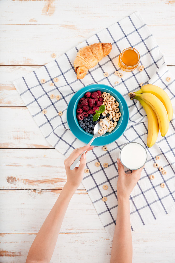 Cereal, berries, banana and croissant and plaid napkin on wooden background