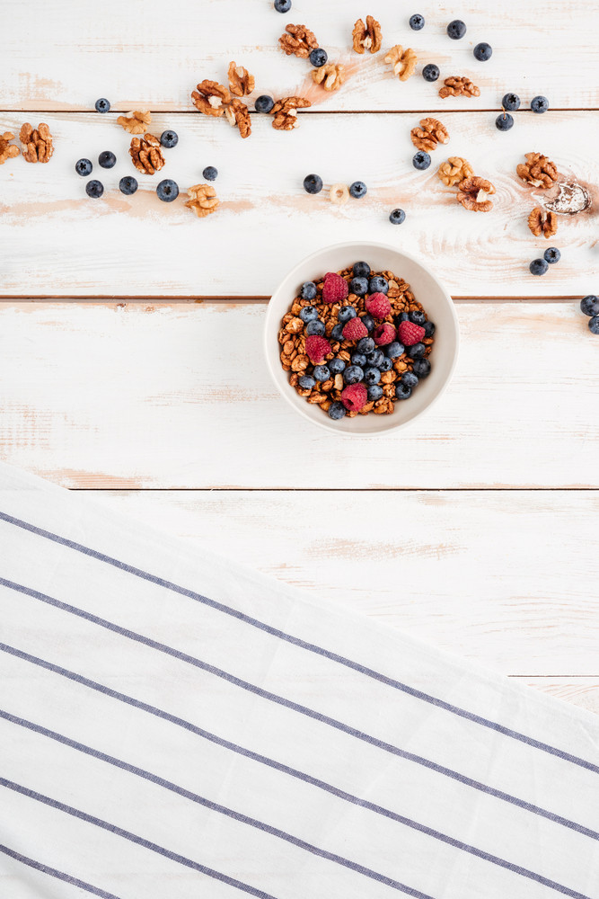 Cereals with berries, nuts and striped napkin on wooden bakground