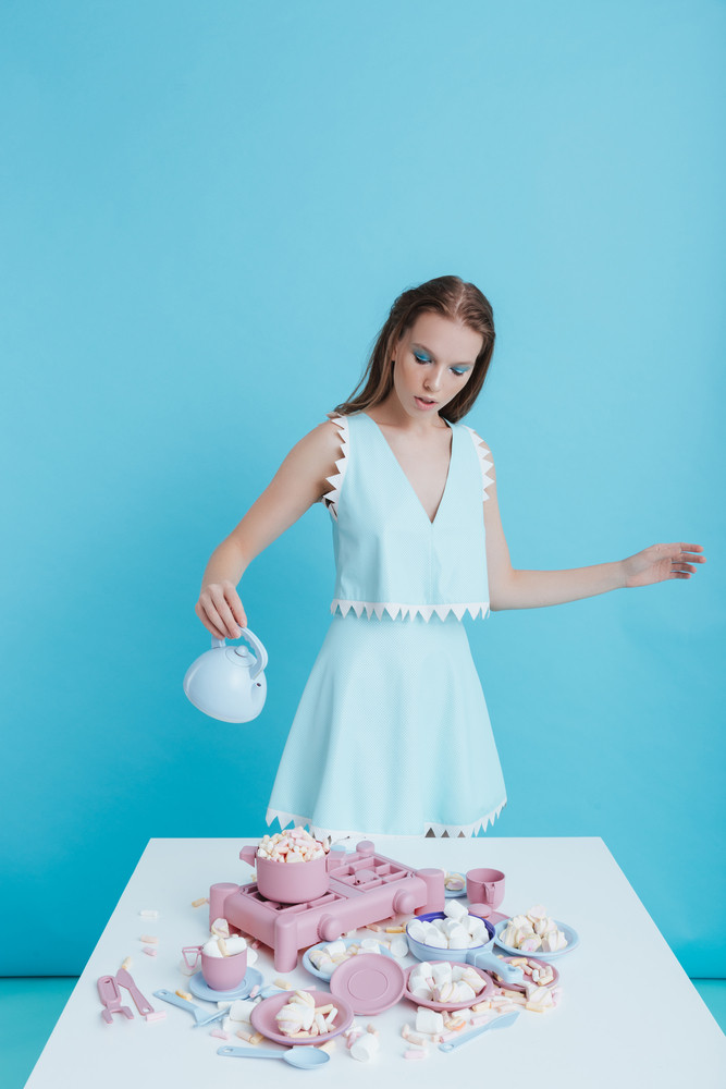 Charming young woman standing and playing with plastic tableware and marshmallows over blue background