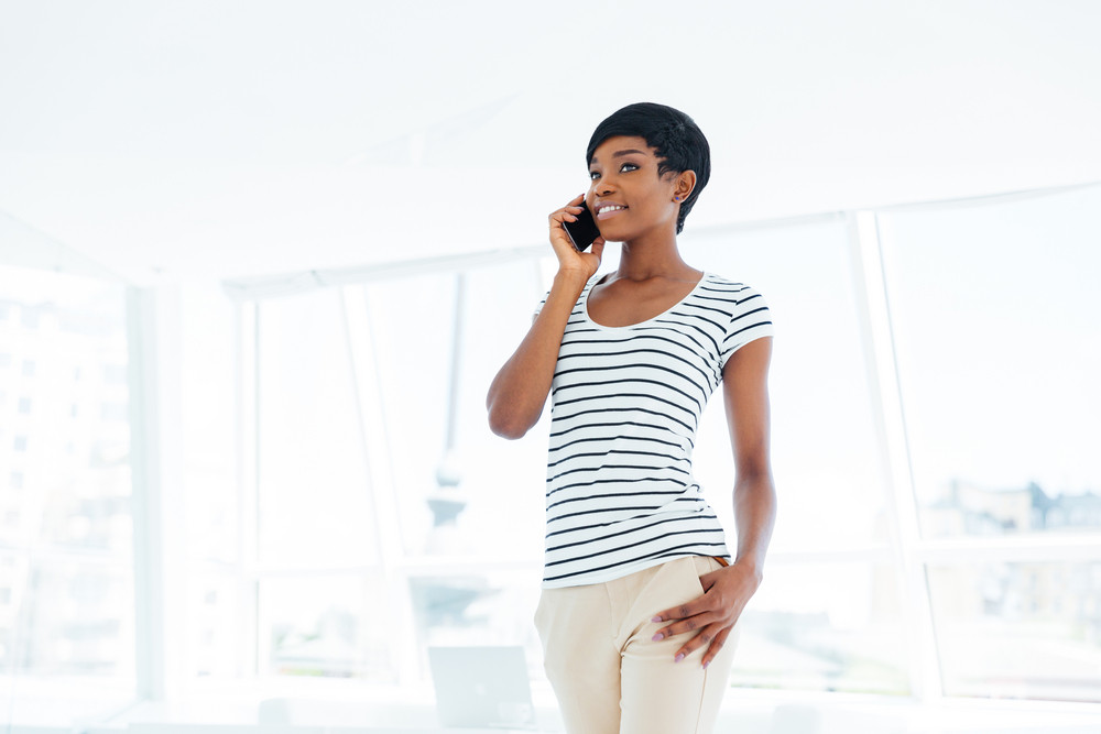 Cheerful african american young businesswoman standing and talking on mobile phone in office