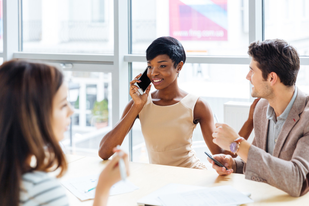 Cheerful african american young businesswoman talking on cell phone on business meeting in conference room