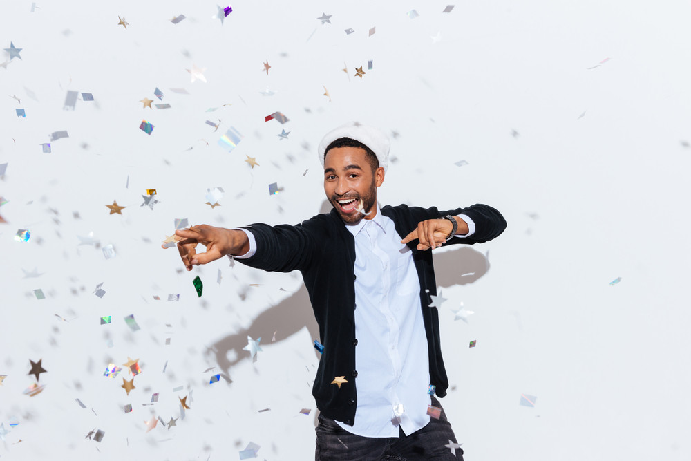 Cheerful african american young man in santa claus hat dancing over white background
