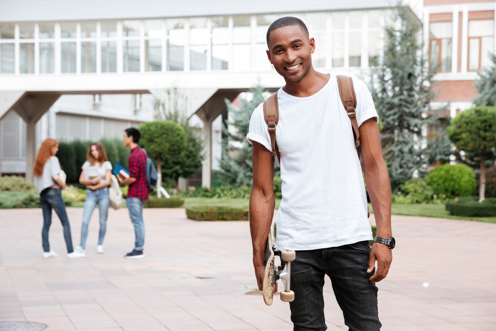 Cheerful african american young man student with backpack standing and holding skateboard outdoors