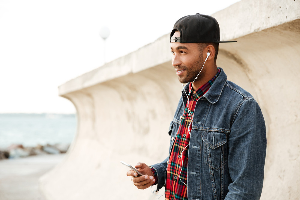 Cheerful african man wearing cap walking on the beach and chatting by his phone while listening music with earphones. Look aside.