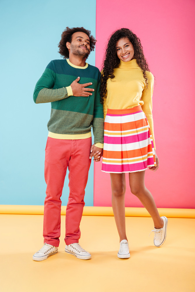 Cheerful african young couple standing and laughing over bright colorful background