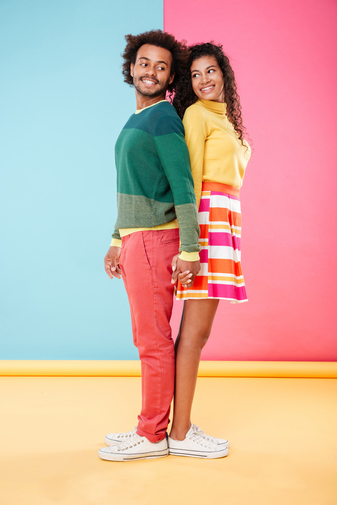 Cheerful african young couple standing back to back and holding hands