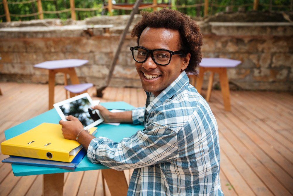 Cheerful african young man in glasses using tablet in outdoor cafe