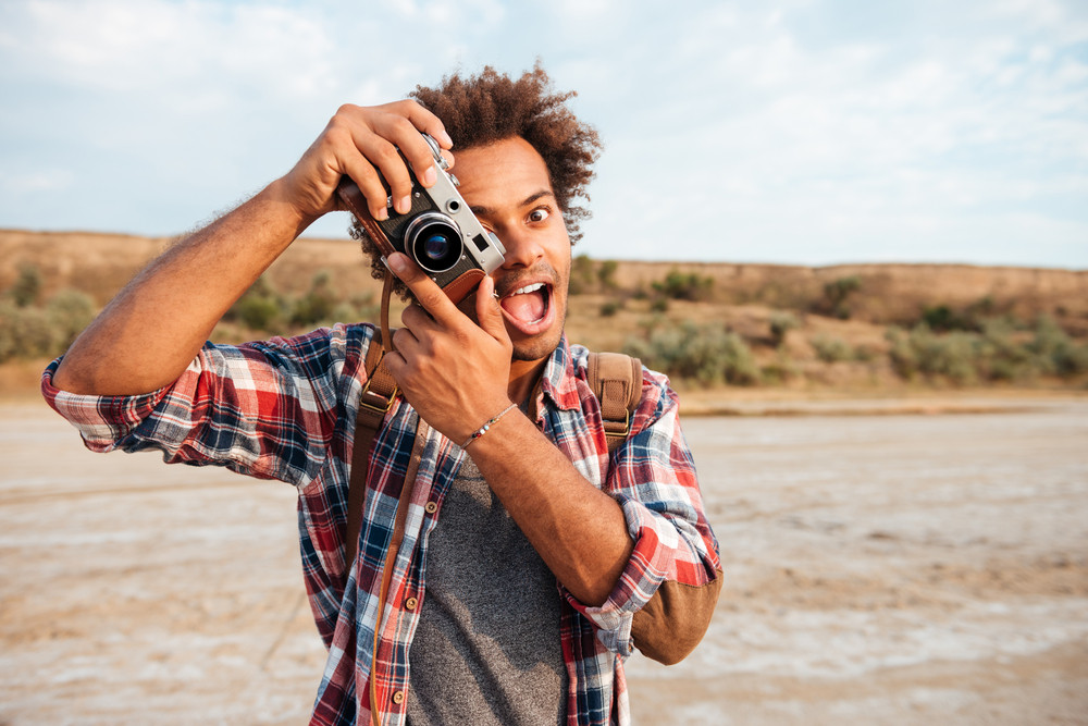Cheerful african young man taking pictures and having fun on the beach