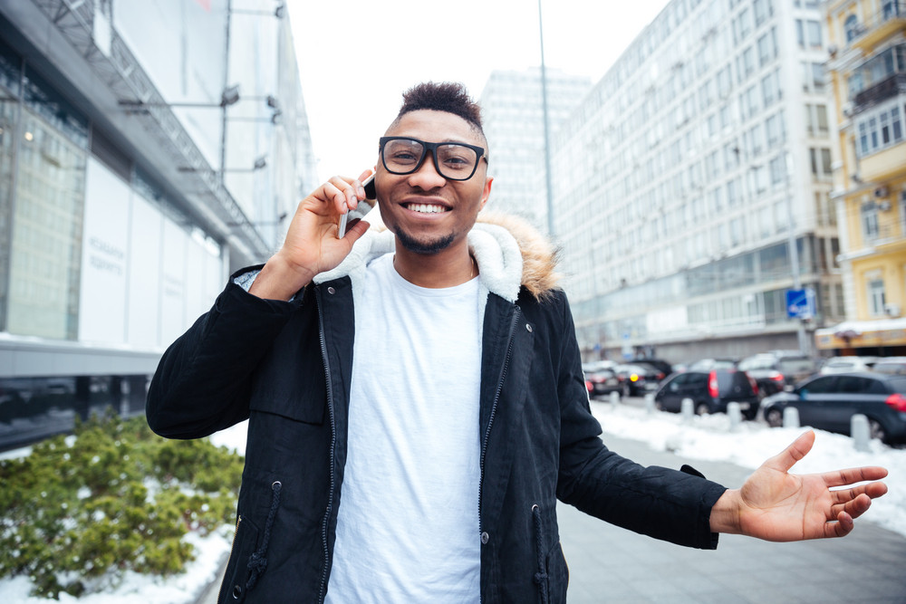 Cheerful african young man walking on the street while talking by his cellphone. Looking at camera.