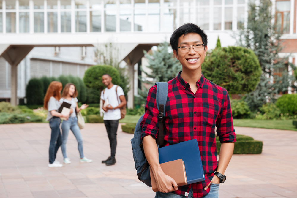 Cheerful asian young man student in glasses standing in campus outdoors