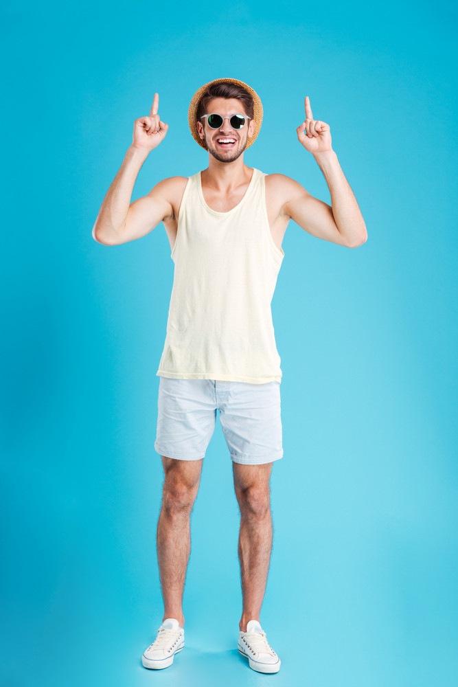 Cheerful attractive young man in hat and sunglasses pointing up with both hands over blue background