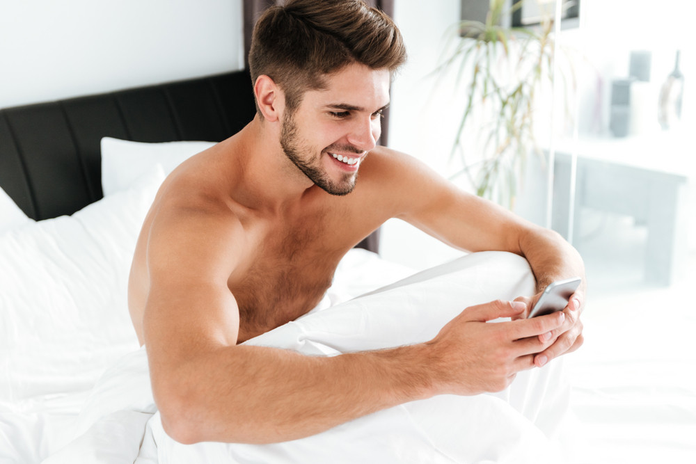 Cheerful attractive young man sitting and using mobile phone in bed