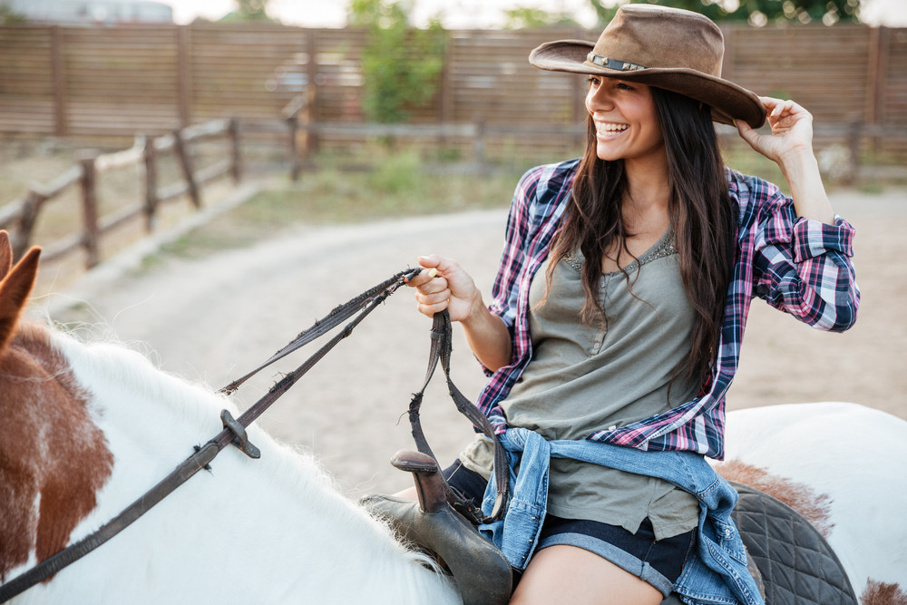 Cheerful attractive young woman cowgirl smiling and riding horse in village