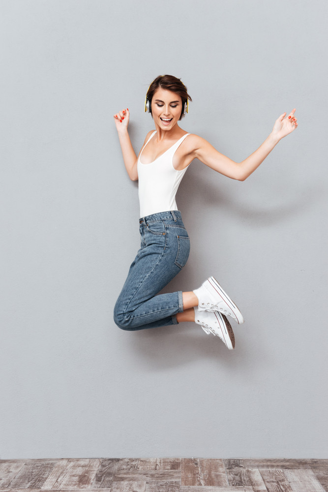 Cheerful attractive young woman listening to music with headphones and jumping in the air over gray background