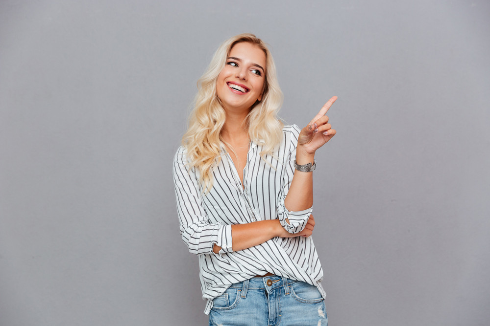 Cheerful attractive young woman pointing finger away over gray background