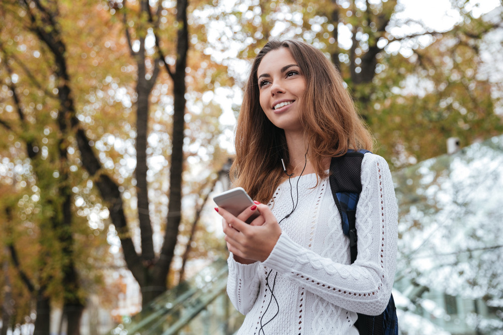 Cheerful attractive young woman smiling and listening to music from mobile phone outdoors