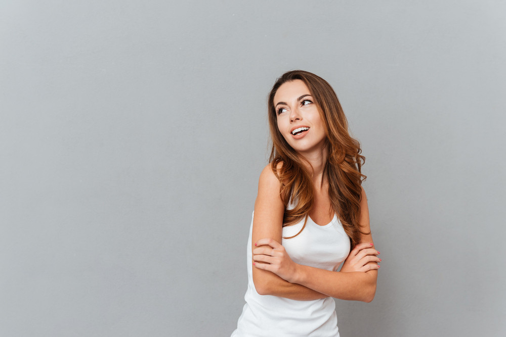 Cheerful attractive young woman standing with arms crossed and looking away at copy space