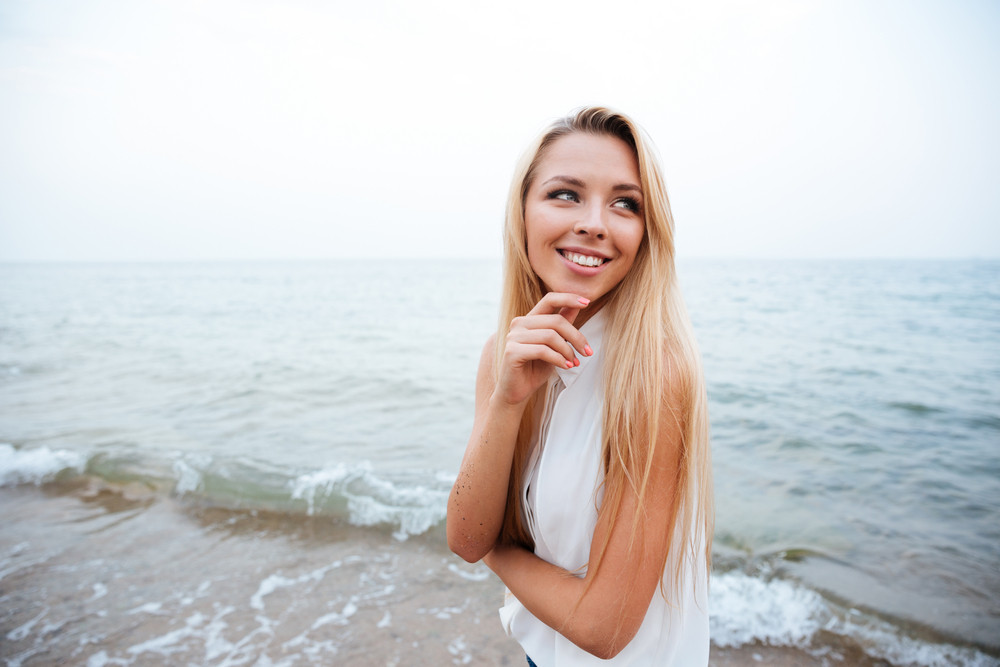 Cheerful attractive young woman walking on the beach