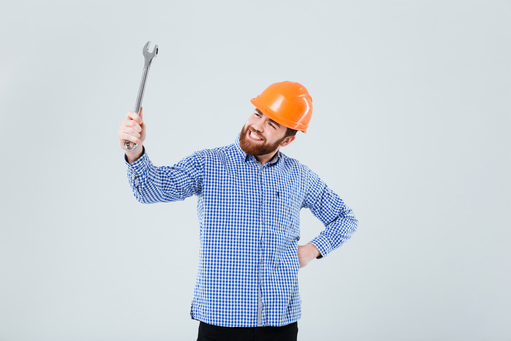 Cheerful bearded young man in helmet holding and looking at wrench