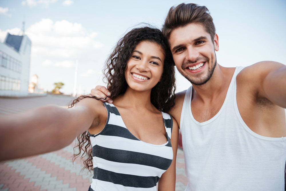 Cheerful beautiful young couple making selfie outdoors together