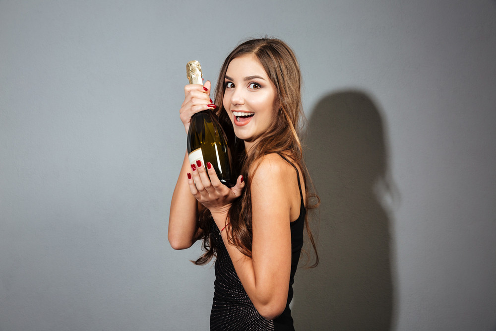Cheerful beautiful young woman in black dress holding bottle of champagne over grey background