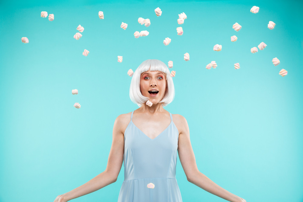 Cheerful beautiful young woman in blonde wig throwing marshmallows in the air over blue background