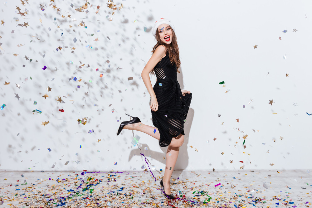 Cheerful beautiful young woman in santa claus hat dancing over white background