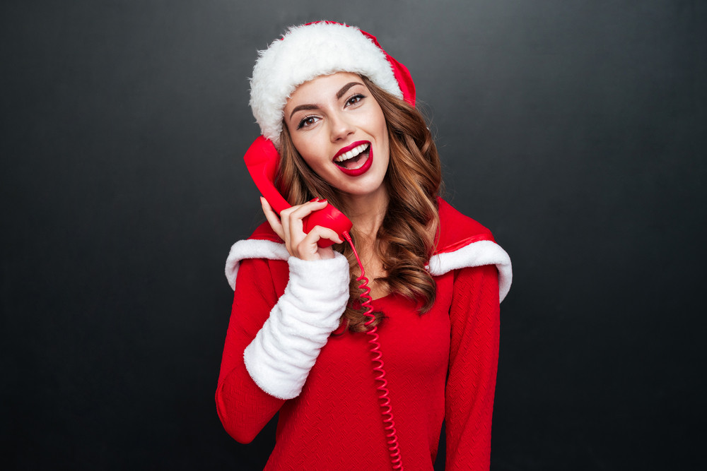 Cheerful beautiful young woman in santa costume standing and talking on telephone over black background