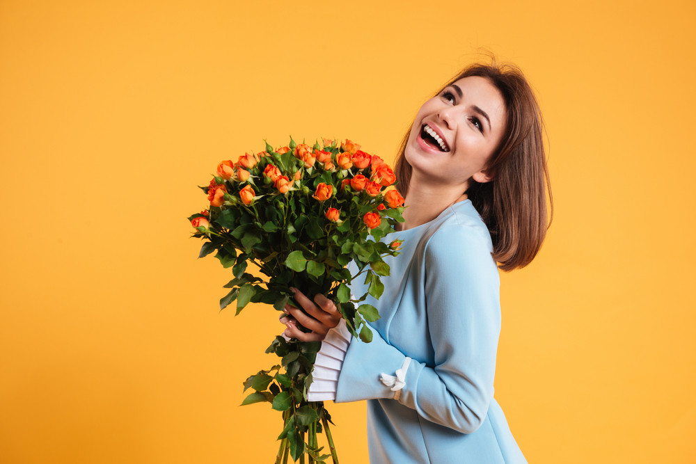 Cheerful beautiful young woman laughing and holding bouquet of flowers over yellow background